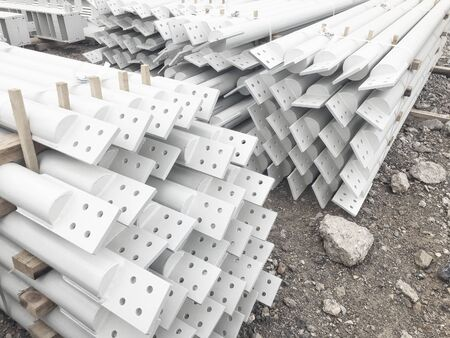 White colored stacked metal diagonal bracings with holes for bolts. Stacked metal parts of a pre-fabricated building. Fast-built camp construction parts at the warehouse.