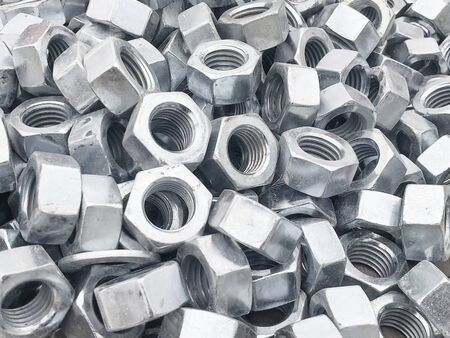 Steel nuts piled in the box. Fastening construction equipment. Fixing hardware.