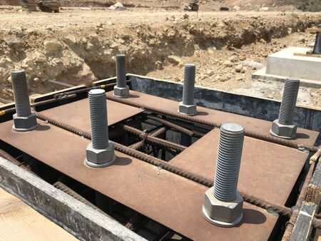 Formwork and reinforcement of concrete reinforced foundation with metal anchor bolts designed for the installation of metal columns.