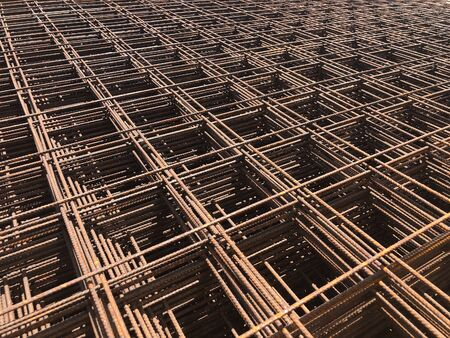 Piled iron reinforcement workpieces. Metal mesh for reinforcement. Iron rusty rectangular structure.
