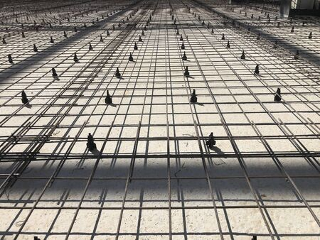 Metal reinforcement grid with plastic holders. Reinforced concrete preparation. Concrete basement construction.