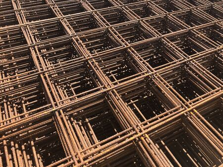 Piled iron reinforcement workpieces. Metal mesh for reinforcement. Iron rusty rectangular structure.