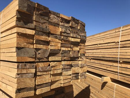 Stack of lumber at the outdoor warehouse. Stockpiled edged boards.