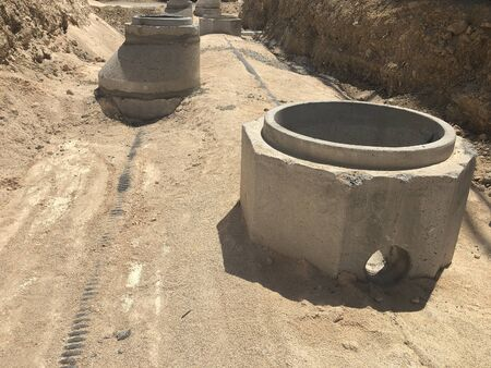Storm water drainage reinforced concrete wells in the dug trench. Water drainage system under construction.
