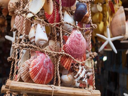 Traditional colorful home decorations made from different shape and color seashells. Souvenir hangings on the tropical sea resort market