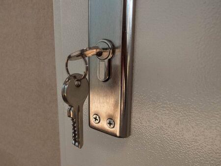 Key on the key chain inside the door keyhole. Stock Photo