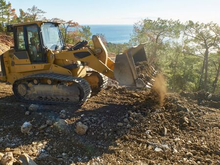Bulldozer is moving soil during road construction works.