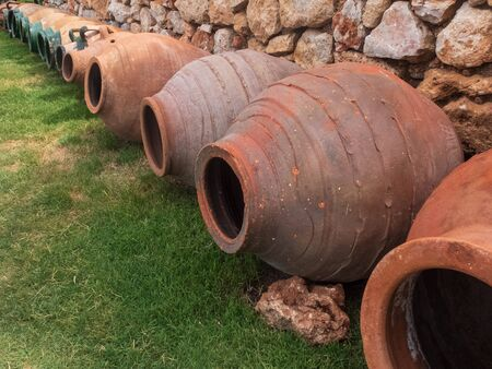 Ancient ceramic amphoras on the green lawn against stone wall.