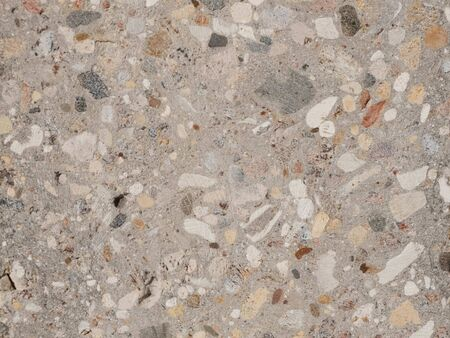 Grinded concrete texture with exposed gravel stones.