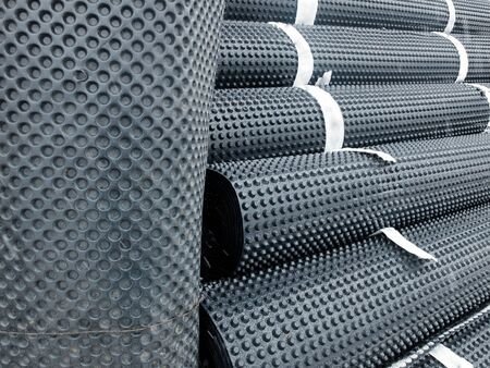 Piles of rolled membrane waterproofing tied with tape. Stock Photo
