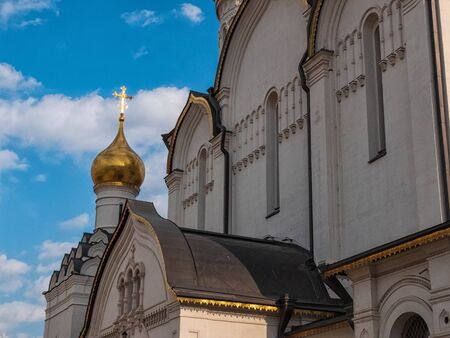 Golden domes of orthodox cathedral against bright blue sky and clouds at background. 写真素材