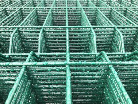 Rain drops on green colored metal grid.