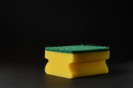 single new yellow sponge against black background.