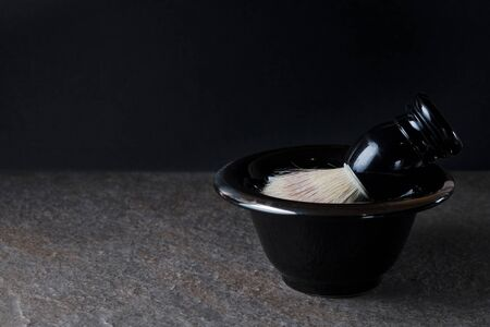 Shaving brush and bowl on the stone surface at black background.