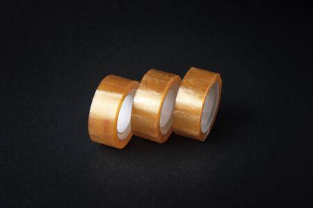 Set of rolled adhesive tape at black background. Reklamní fotografie