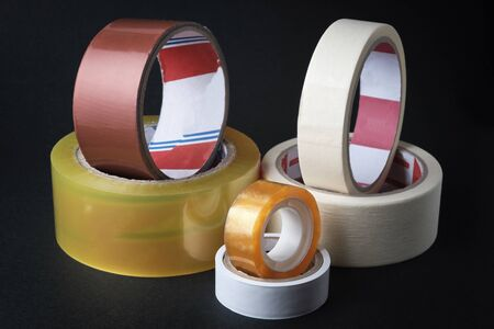 Set of different rolled adhesive tape at black background.