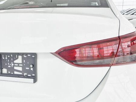 Tail lights of new white korean sedan car in the car dealer showroom. Stock Photo