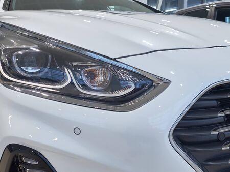 Headlights of new sedan car in car dealer showroom.