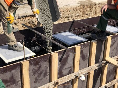 Construction workers are pouring concrete to formwork.
