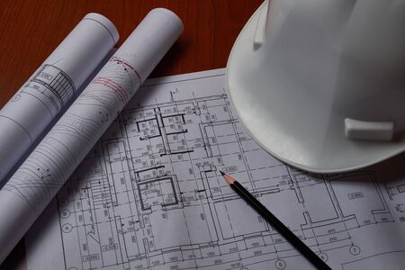 White hardhat and drawings at engineer workplace.