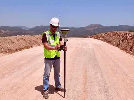 Geodetic engineer surveyor in white hard hat doing measurements with GNSS satellite receiver during road construction works. Foto de archivo