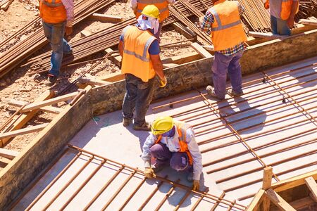 Workers are building concrete reinforced foundation plate at construction site.
