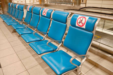 Row of chairs with social distancing signs at airport