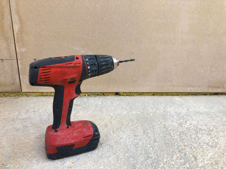 Cordless screwdriver on concrete surface against drywall. Electric power tools.