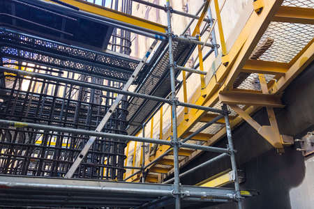 Metal scaffoldings at construction site. Auxiliary supporting building structures.