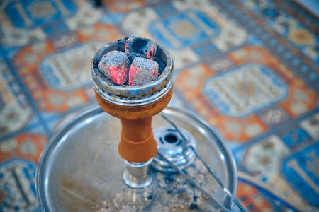 Embers on hookah bowl against traditional arabic style carpet