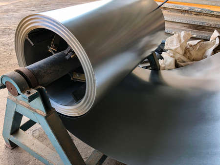Rolled halvanized metal at construction site workshop. Tinsmith metal material. Stock Photo