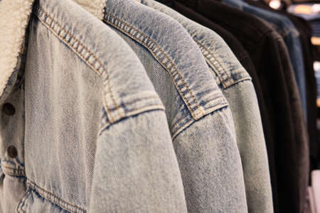 Sherpa jackets on coat hangers. Casual warm denim jackets at retail store. Banco de Imagens