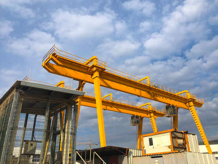 Gantry cranes opposite cloudy sky. Industrial lifting machinery. Hoist, winch Stock Photo