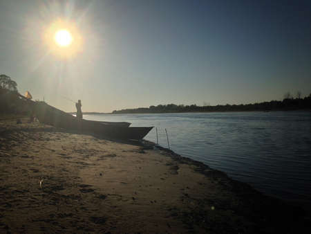 Silhouette of fisherman casting his fishing rod. Landscape of river and fishermen boats at sandy beach in summer morning Stock Photo