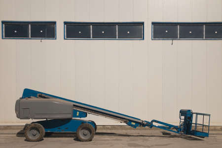 Lifting vehicle platform parked near industrial building