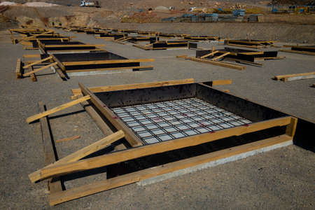 Row of concrete foundation formworks at construction site