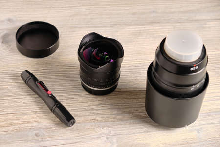 Fisheye lens, telephoto zoom lens and pen for lens cleaning at table Stock Photo