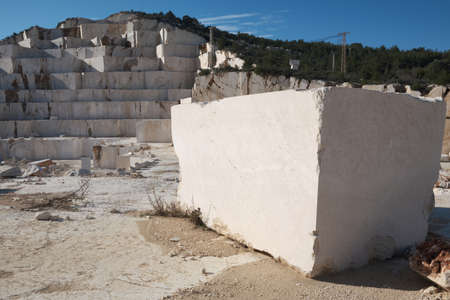 Marble block on foreground and quarry at background