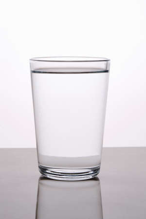 Blank glass of water captured with reflection with back lighting against light background