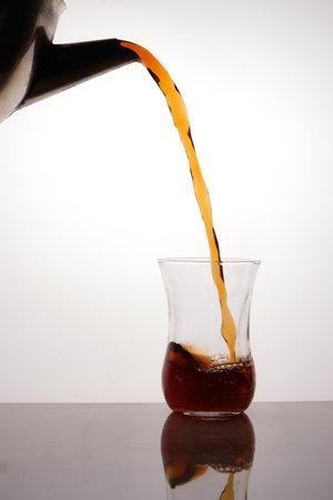 Tea pouring from blackened teapot to turkish tea glass