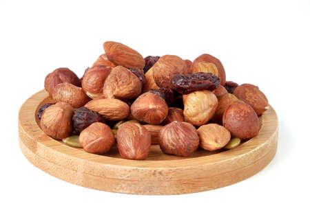 Hazelnut and almond kernels, raw pumpkin seeds and raisins on bamboo plate