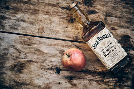Jack Daniels Honey liqueur and apple fruit at weathered wooden background