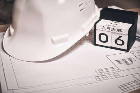 Engineering drawings, white hardhat and calendar showing September 6 date Stock Photo