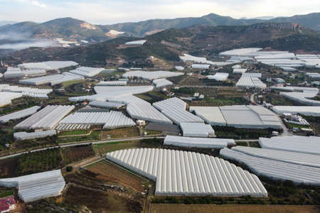 Numerous greenhouses at rural hillside area aerial view Stock Photo
