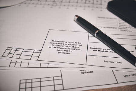 Engineering drawings and black pen at desk Stock Photo