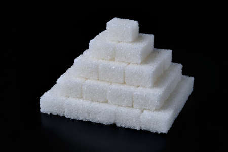 Stack of white sugar cubes at black background