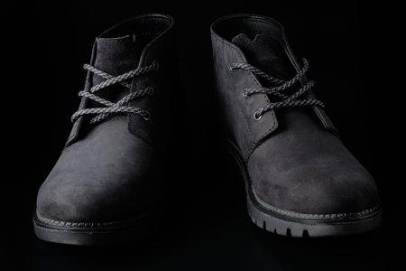 Black mens suede shoes at black background