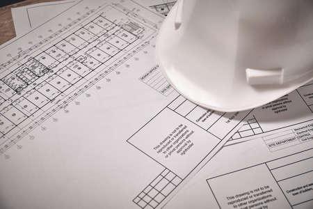 Blueprints and white hardhat at desk