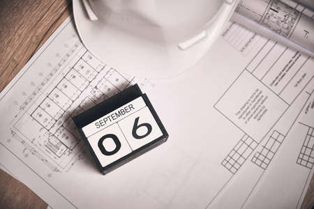 Engineering blueprints, white hardhat and calendar showing September 6 date Stock Photo