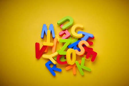 Colorful plastic letters messed up on yellow background